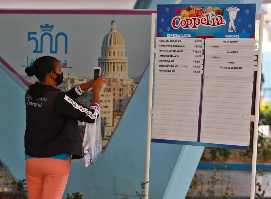 Una mujer toma fotos a un tablero con los precios de la heladería Coppelia